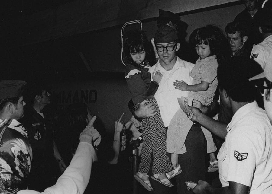 American soldier carrying two small Asian children, deplaning.