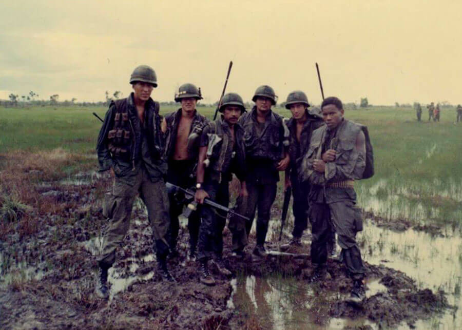 Six soldiers standing in muddy rice paddy fields.