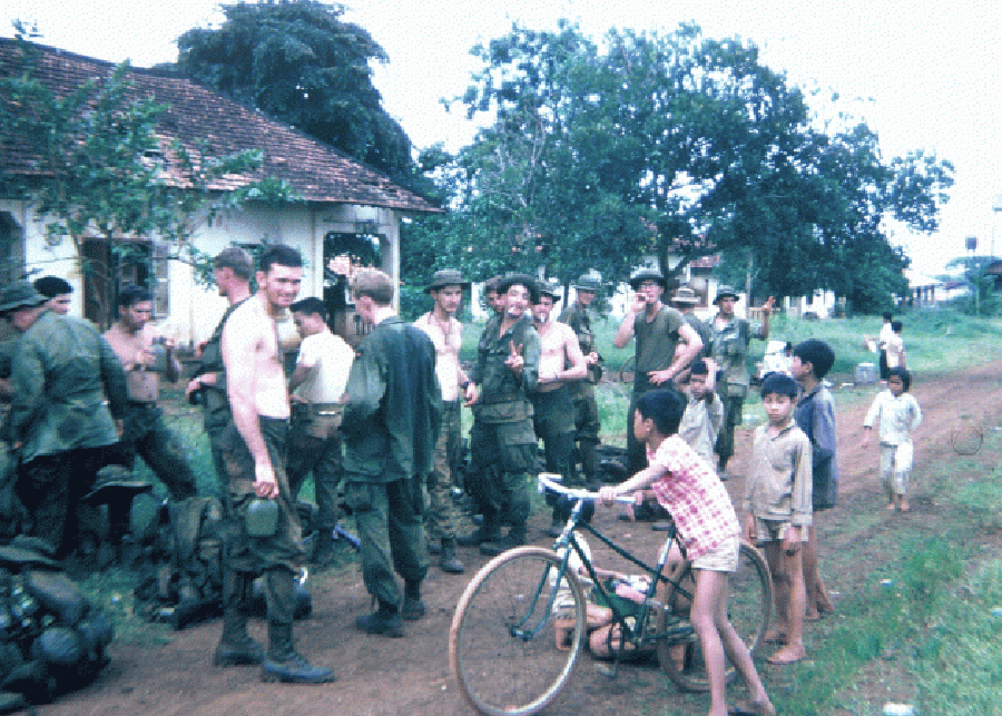 A group of U.S. soldiers and young Asian children with bicycles.