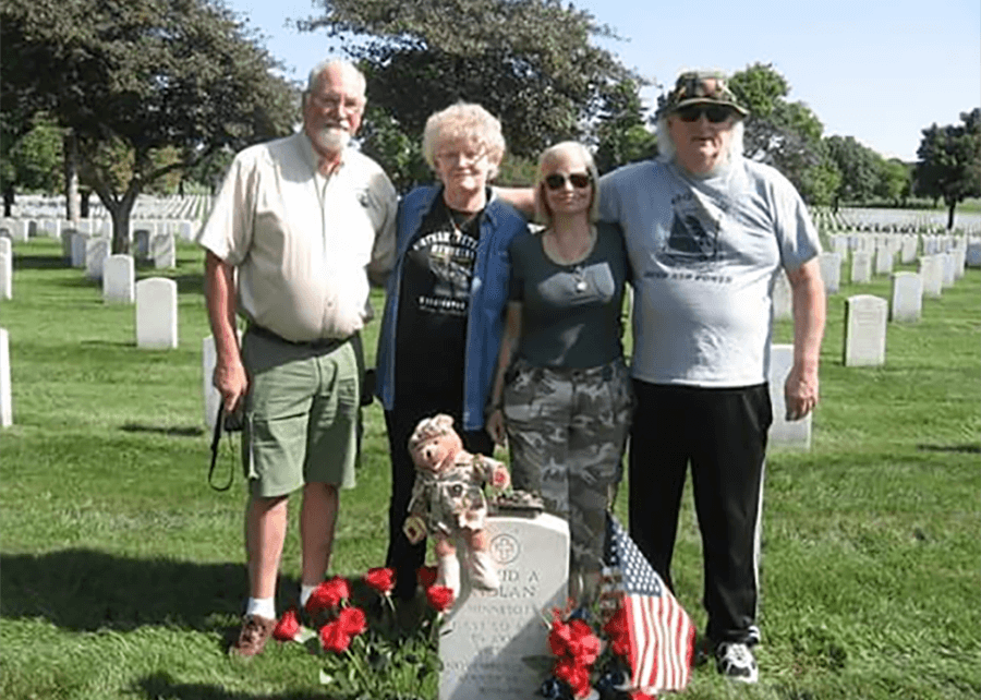 Contemporary photo of four people standing behind a white marble tombstone decorated with a miniature American flag, teddy bear in uniform, red carnations.