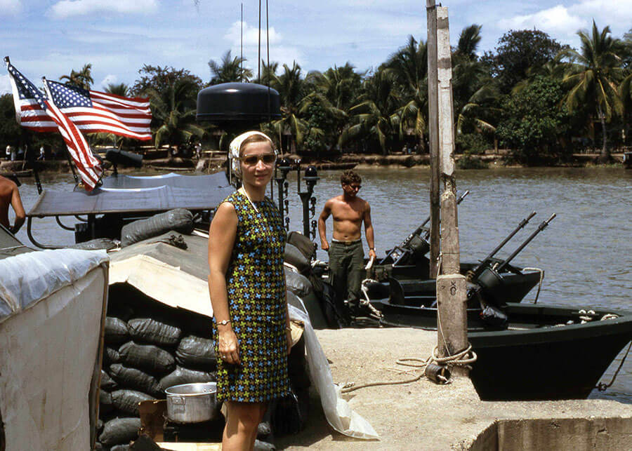 Young woman posing for a photo on a River Patrol Boat with American flags flying