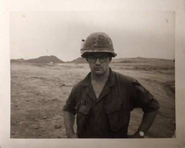 Stern-looking US soldier with his hands on his hips, standing in a dusty expanse with short mountains in the distance behind him.