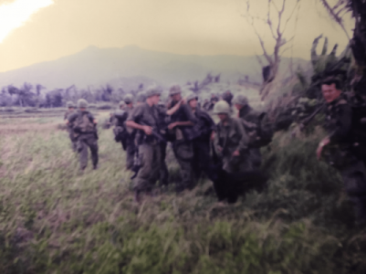 Blurry image of a group of soldiers and a black dog, standing in a vegetated area.