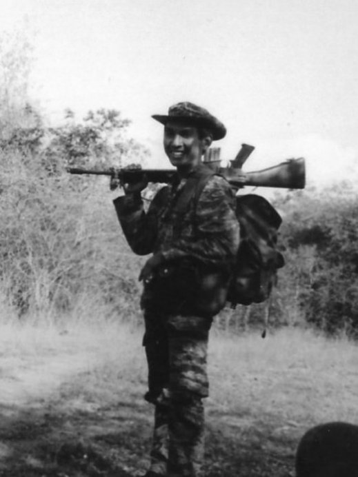 Cambodian soldier with gun over his right shoulder.
