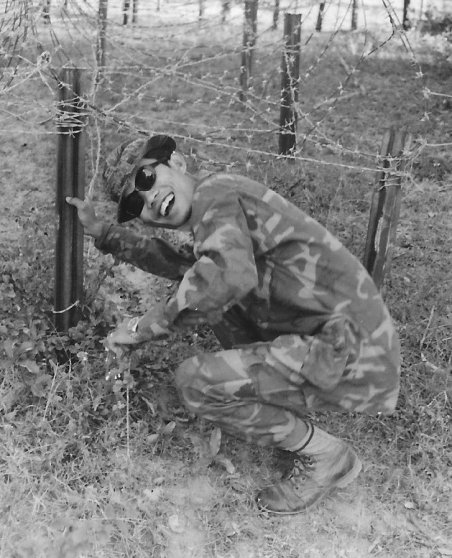 Cambodian soldier crouching by barbed wire fence.