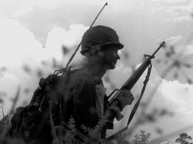 Black and white photo of a soldier holding a gun.