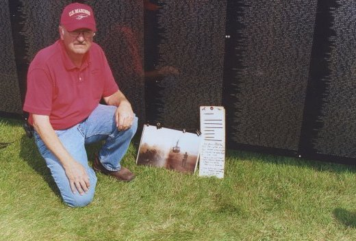 Contemporary photo of an aged U.S. veteran crouching down by tributes laid against a scaled-down replica of the Vietnam Wall.