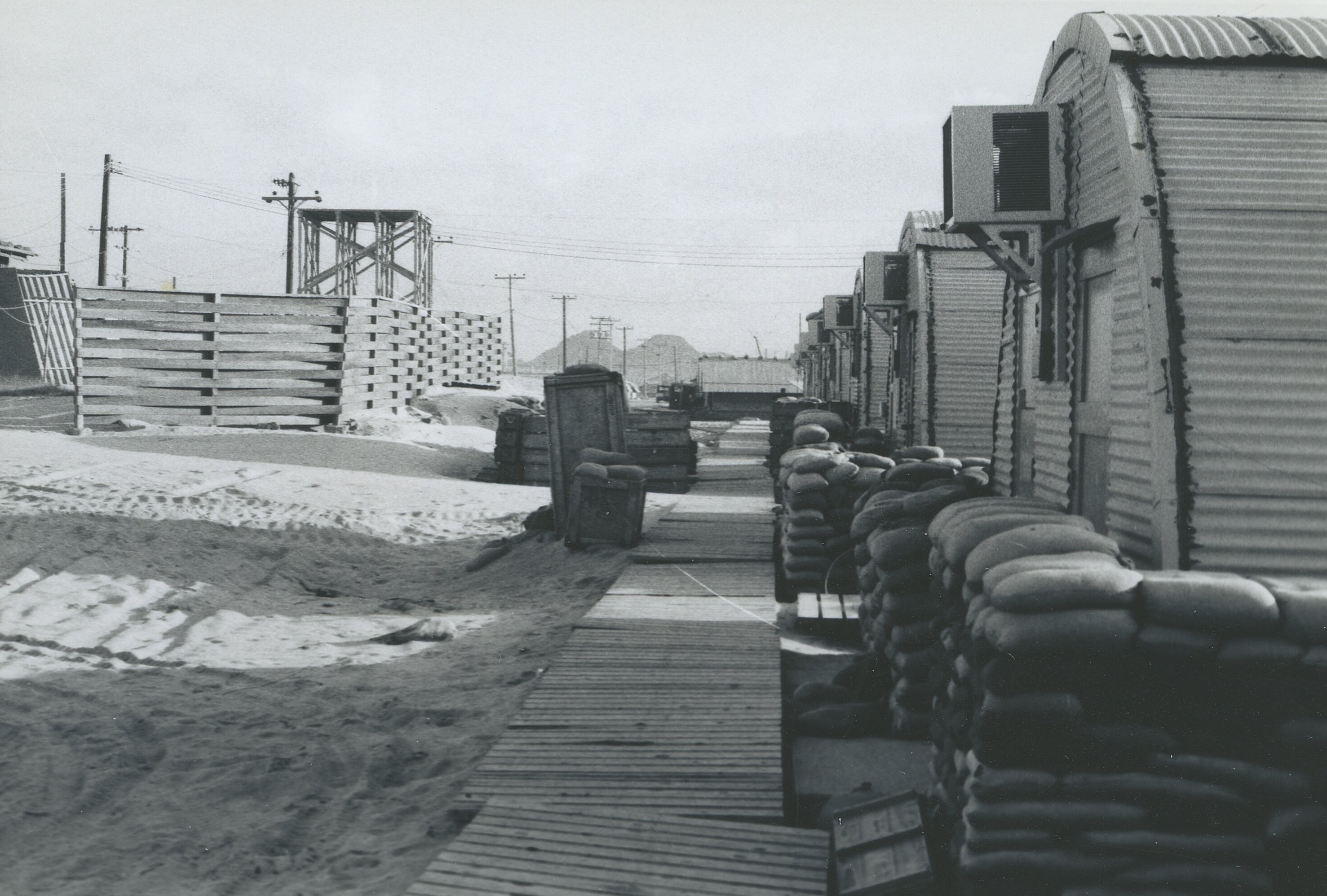 Squat corrugated steel buildings with sandbags stacked around them.