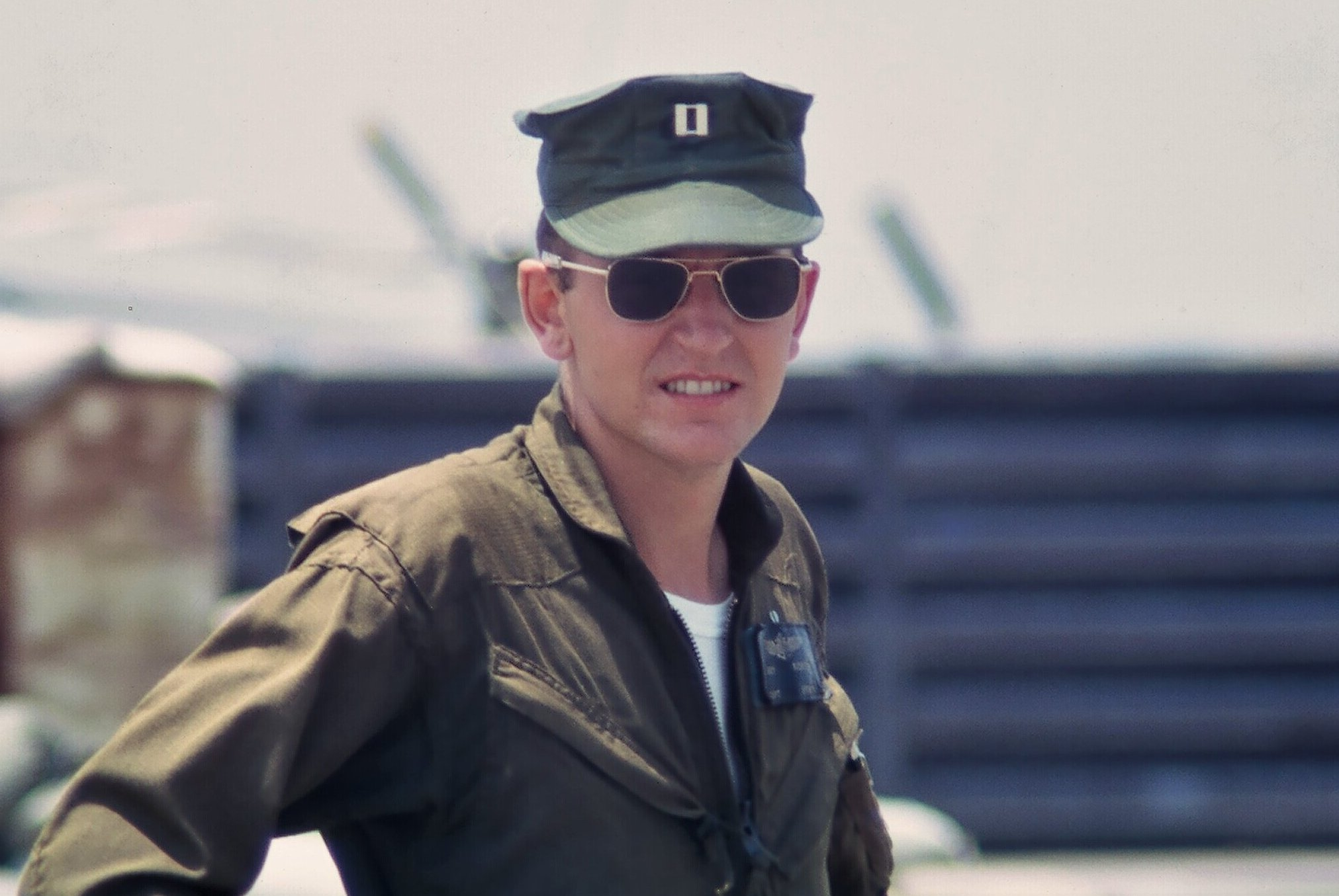 A young soldier wearing a cap, a flight jacket, and aviator sunglasses.