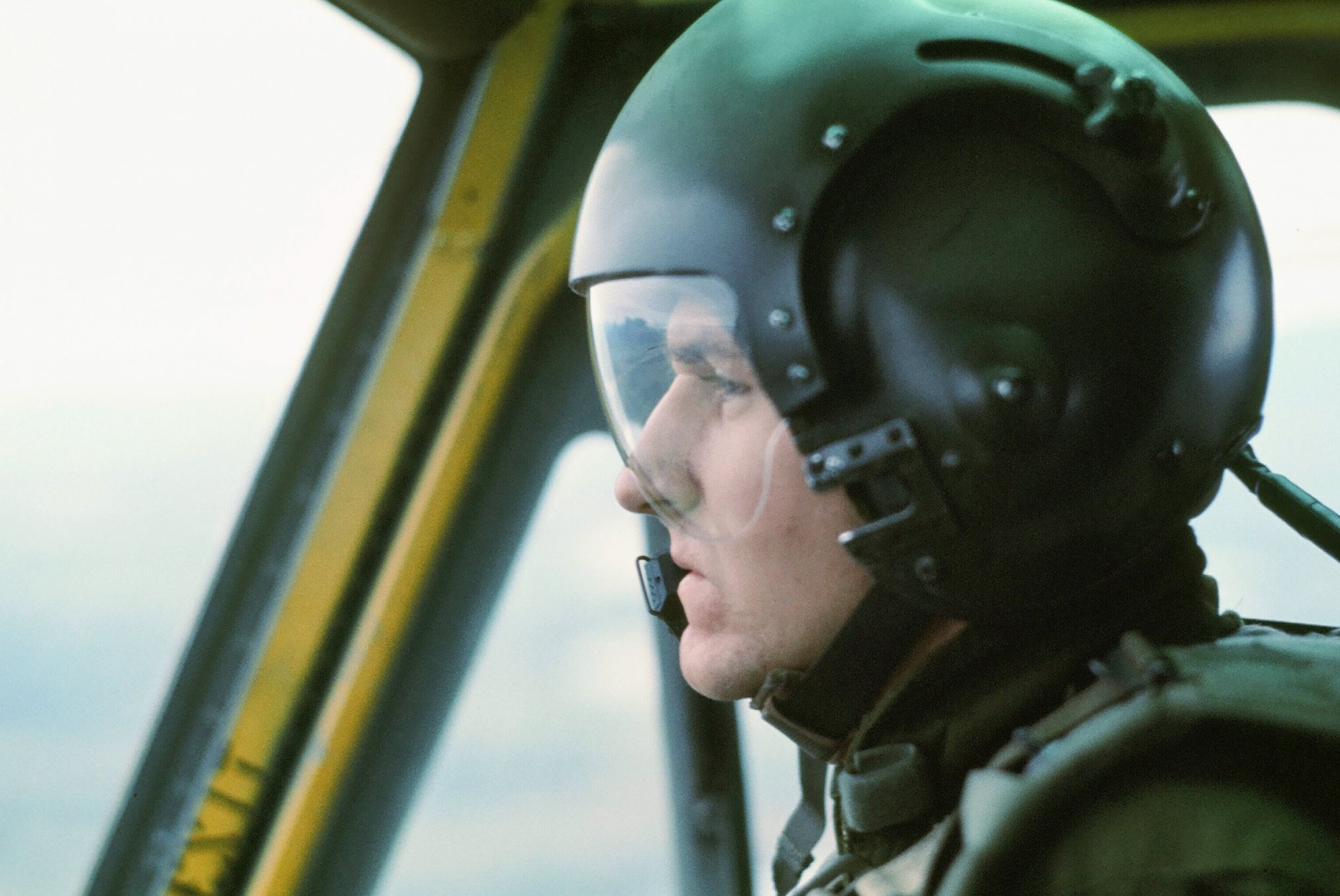 A profile of a young pilot in a plane, wearing a helmet and goggles.