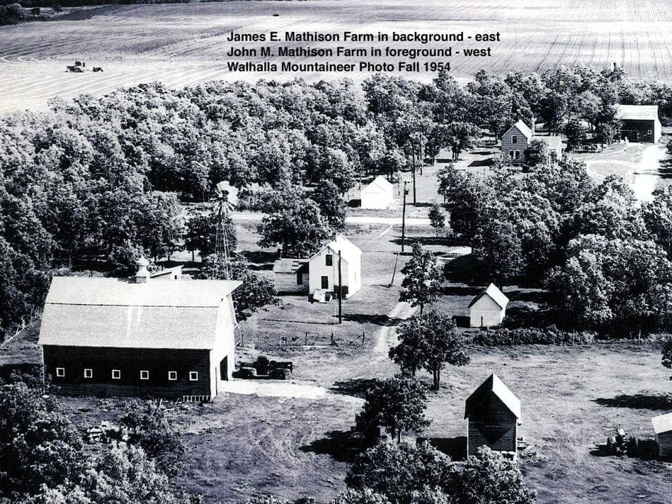 """Aerial view of farm lands. Text on photo reads: """"James E. Mathison Farm in background - east. John M. Mathison farm in foreground - west. Walhalla Mountaineer Photo Fall 1954."""""""