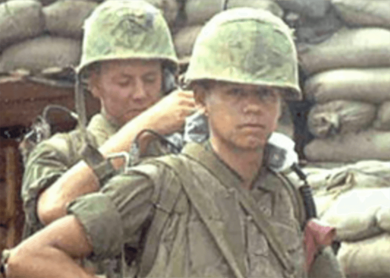 A stern-looking soldier looks at the camera while a fellow soldier fills his backpack.