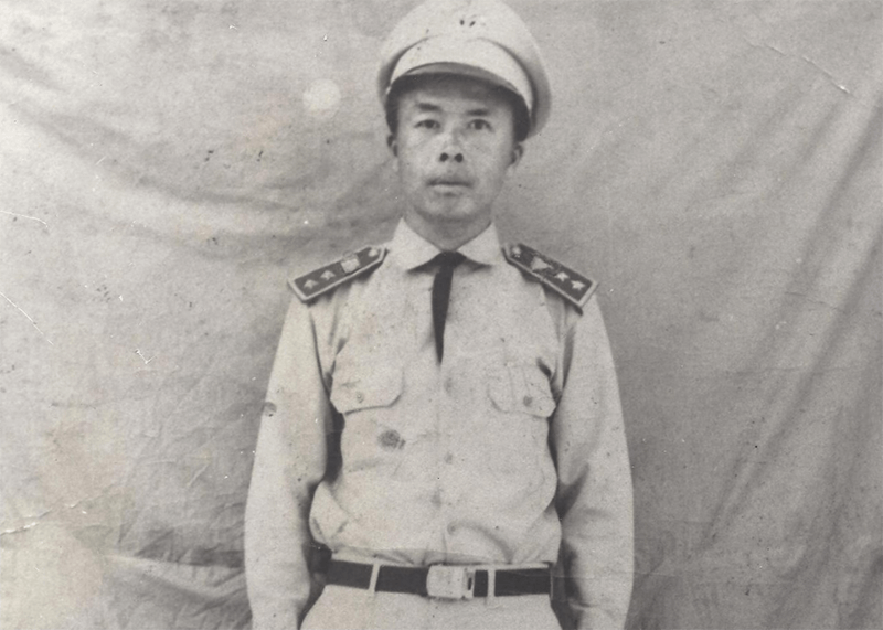 A photo of a young Asian man in uniform, posing for a photo.