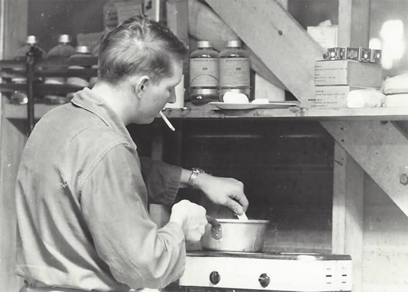 A soldier with a cigarette, cooking over a pot in a kitchen.