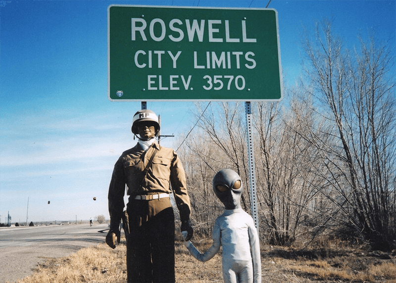 A mannequin in a uniform holding the hand of a shorter alien figure in a white space suit, posed in front of a Roswell City Limits sign.