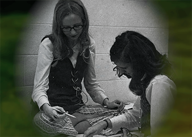 Two young women sitting cross-legged, looking at something on the floor in front of them.