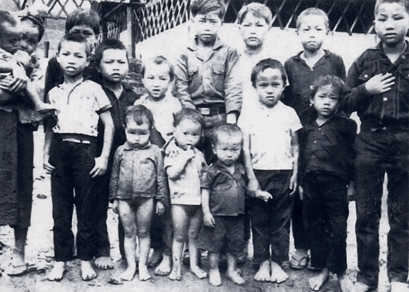 About a dozen Asian children lined up for a photo.