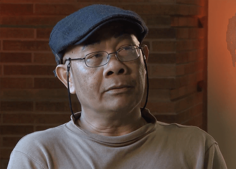 Contemporary portrait of a middle-aged Asian man in glasses and a black cap.
