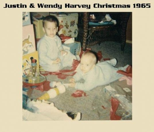 """A toddler and an infant in blue pajamas, playing with toys on the floor. Text in photo margins reads: """"Justin and Wendy Harvey Christmas 1965""""."""