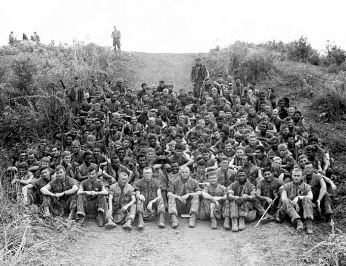 A large company of US soldiers sitting on a hill, posing for a photo.