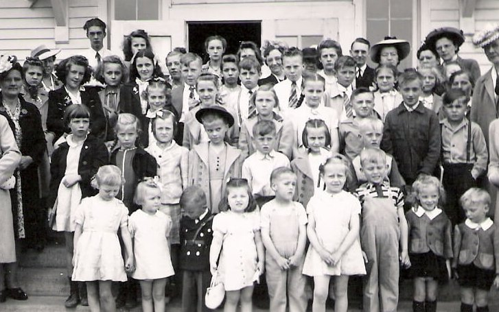 A class photo of students in Sunday clothes, ranging in age from toddler to high schooler, along with adult teachers, presumably.