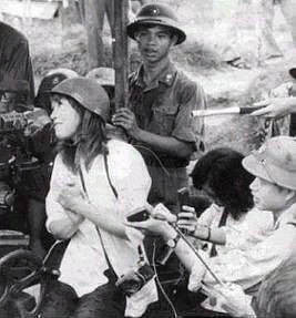 Jane Fonda wearing a white shirt and army helmet, sitting on an anti-aircraft gun and talking to locals and reporters.