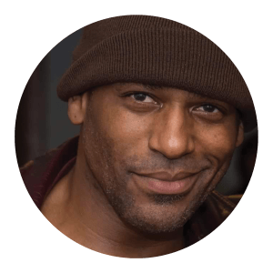 Circular portrait of a smiling African American man.