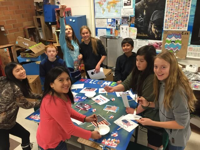 Contemporary image of middle school students around a classroom table, decorating a patriotic-looking school project.