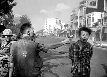 An Asian man shooting another Asian man point blank in the temple on the streets of Saigon.