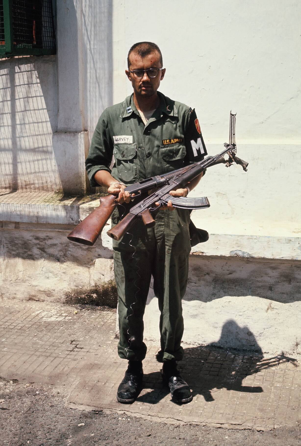 Military police officer holding two guns, standing out on the street.