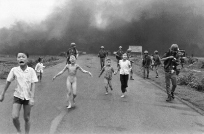 Group of soldiers and crying children, one naked, moving on foot away from a distant cloud of smoke rising from the ground.