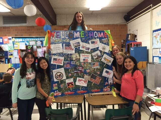 "Contemporary image of middle school girls posing with a patriotic-looking board that says ""Welcome Home"" and is decorated with flags and glitter."