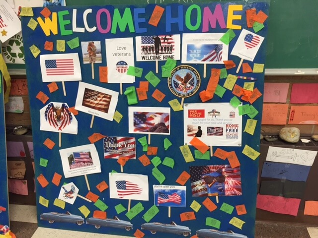 "Contemporary image of a middle school project--a patriotic-looking board that says ""Welcome Home"" and is decorated with flags."