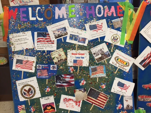 "Contemporary image of a middle school project--a patriotic-looking board that says ""Welcome Home"" and is decorated with flags and glitter."