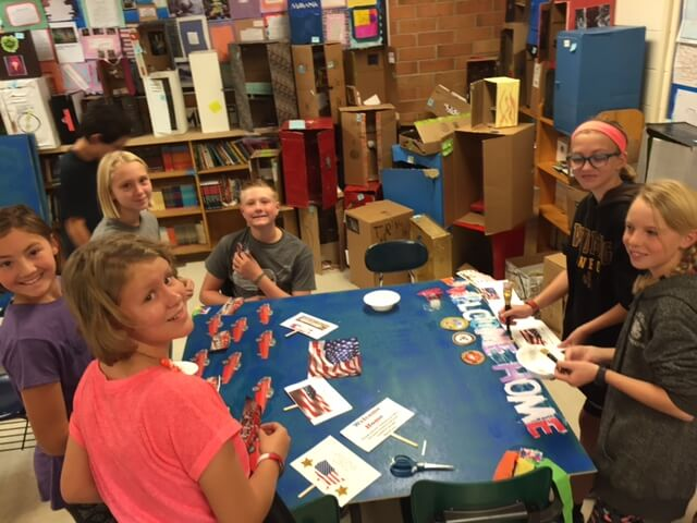 Contemporary image of middle school girls and a boy around a classroom table, decorating a patriotic-looking school project.