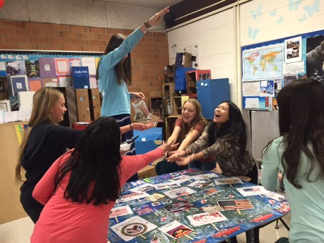 Contemporary image of middle school girls around a classroom table, decorating a patriotic-looking school project.