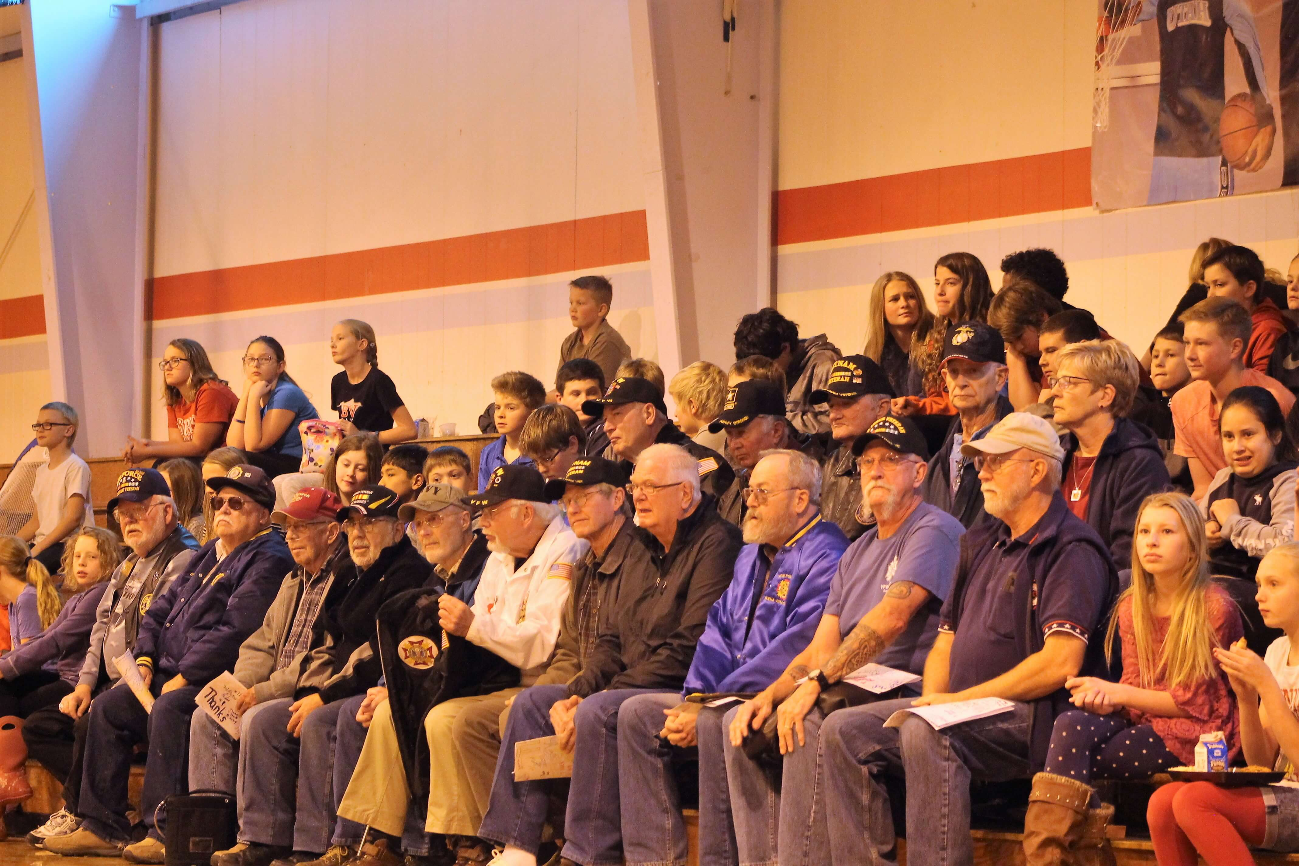 Contemporary image of veterans and middle school students sitting in bleachers for an assembly.