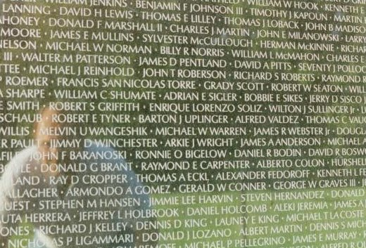 """Reflection of a man in the Vietnam Wall. The name """"Barton J. Uplinger"""" is near the center of the image."""