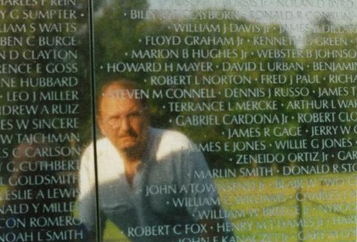 """Reflection of a man in the Vietnam Wall. The name """"Robert Norton"""" is near his head."""