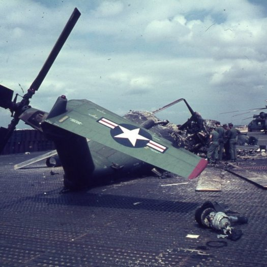 A damages air craft on the ground and with four men inspecting it.