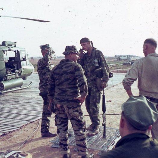 A group of five men in uniform, talking.