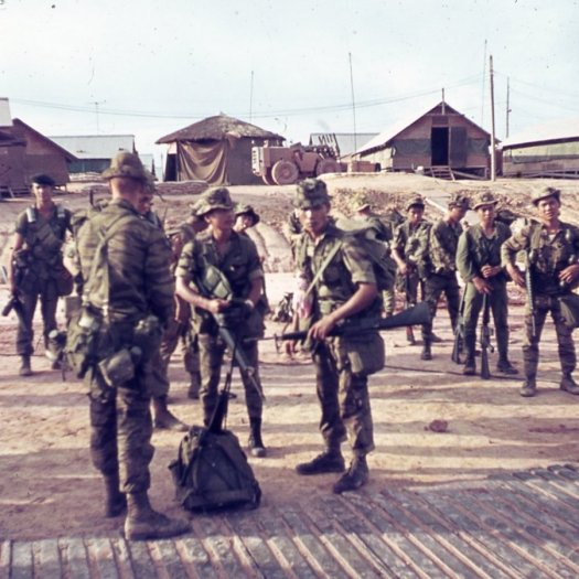 A group of U.S. and Asian soldiers in full gear, standing and waiting around.