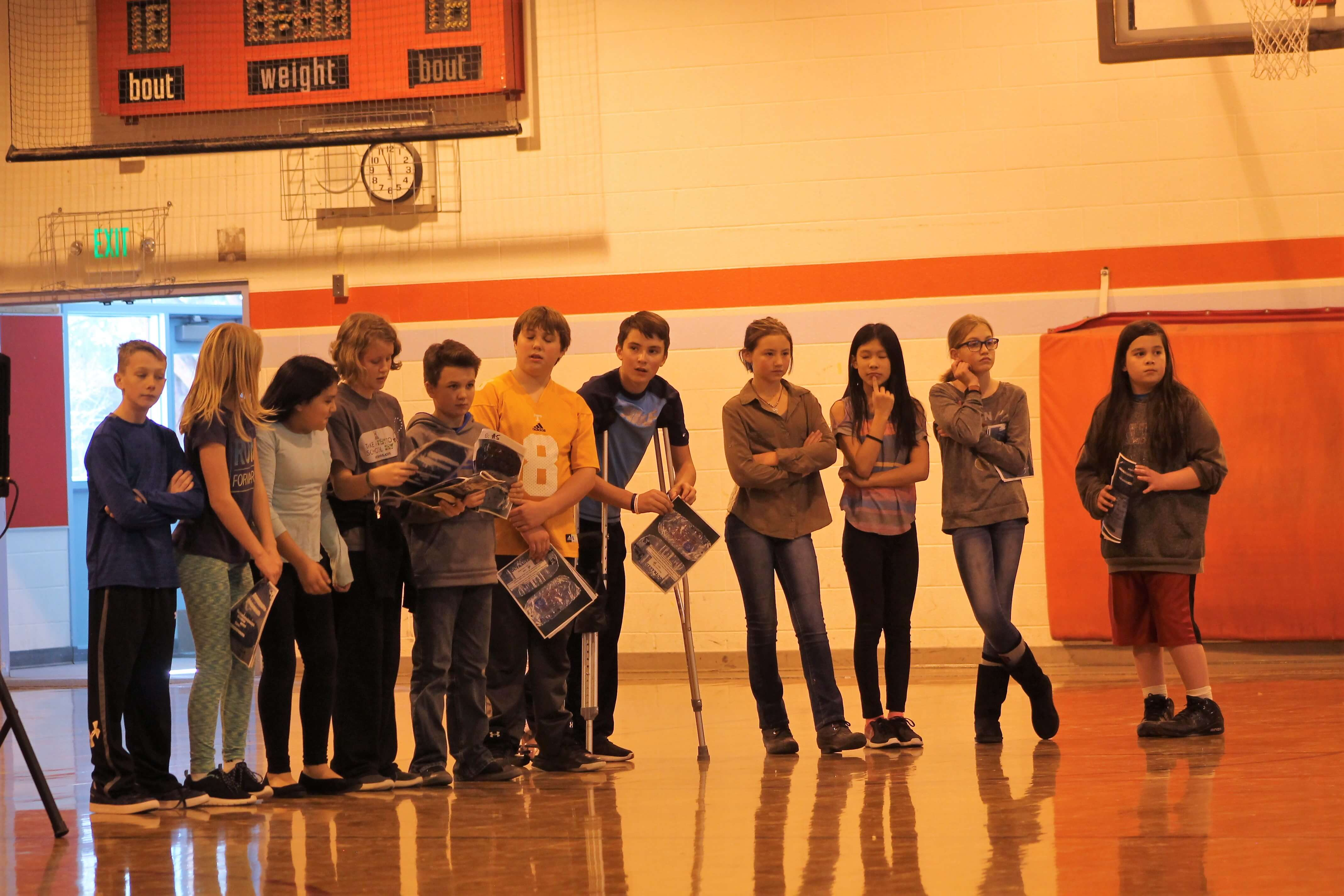 Contemporary image of middle school students lined up in a gymnasium.
