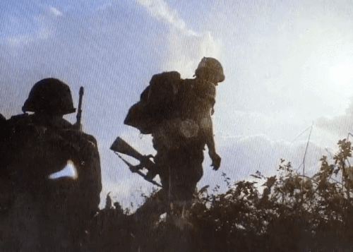 Two silhouetted soldiers against a sunny sky.