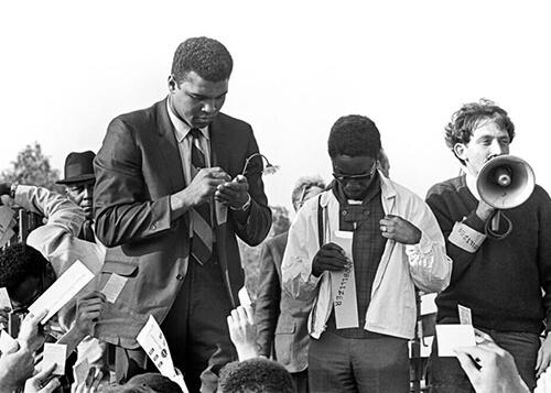 Muhammad Ali signing draft cards.