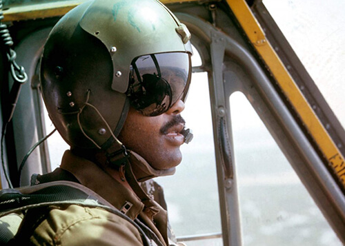 A young black pilot with his helmet and shades on, flying his aircraft.