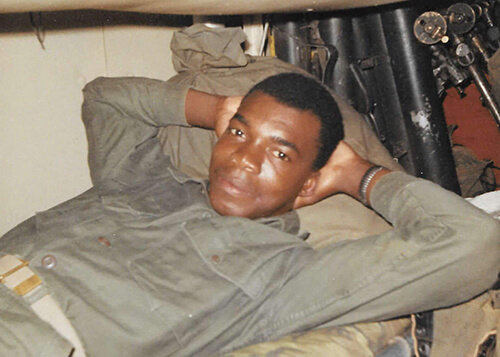 A young black soldier, laying with his hands behind his head.