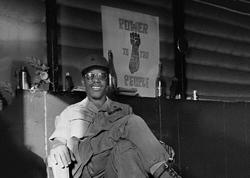 Black GI sitting in front of a Black Power poster.