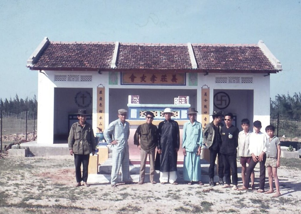 A group of Asian men and boys standing in front of a mausoleum.