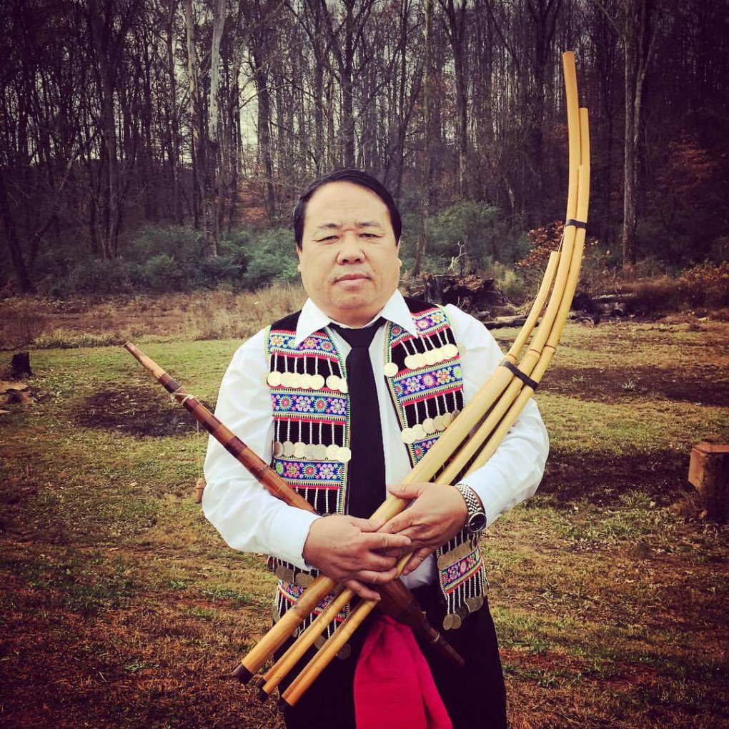 Hmong man holding a bamboo instrument.
